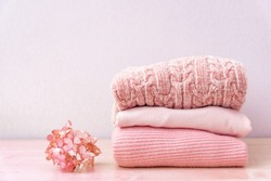Stack of folded wool knitted sweaters or pullovers in pink pastel colors on table with flower hydrangea. Close up of warm cozy comfortable monochrome clothes for autumn winter season.
