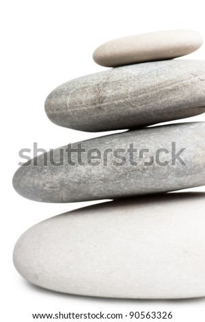 Stack of four round stones isolated over white background