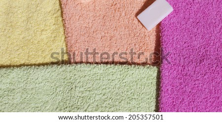 Stack of fresh clean towels and scented soap isolated on white background