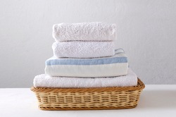 Stack of fresh clean towels in the wicker basket on the white table against bright wall