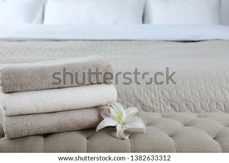 Stack of fresh towels with flower on soft bench in bedroom. Space for text #1382633312