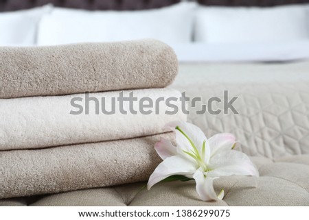 Stack of fresh towels with flower on soft bench in bedroom. Space for text #1386299075