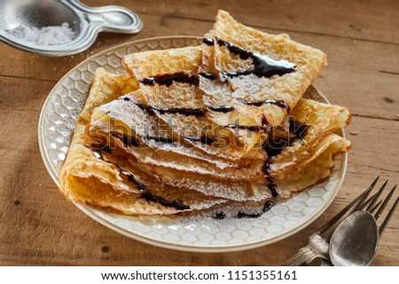 Stack of freshly made fried sugared Crepes drizzled with chocolate sauce and serves on a plate with a vintage sugar spoon or strainer on a wooden table