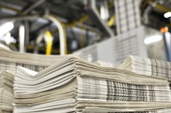 stack of freshly printed daily newspapers transported to a printing plant, in the background machines and technical equipment of a large printing plant