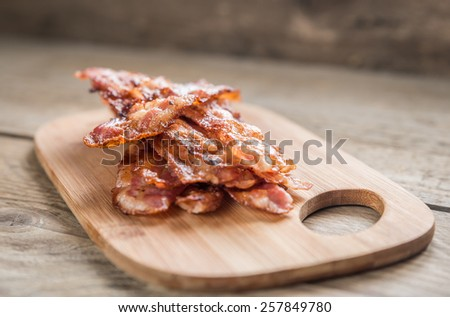 Stack of fried bacon strips on the wooden board