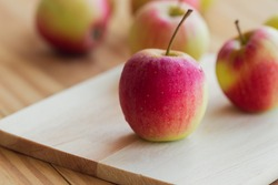 Stack of fuji apple and on cutting board put on wood table with copy space for background or wallpaper. Delicious sweet and juicy fruits for salad cooking or bakery. Fuji apple has origins in Japan.