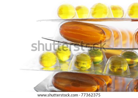 Stack of gel nutritional supplement capsules in blisters on white background.