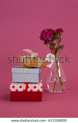 Stack of gift boxes and flowers vase on pink background #651508000
