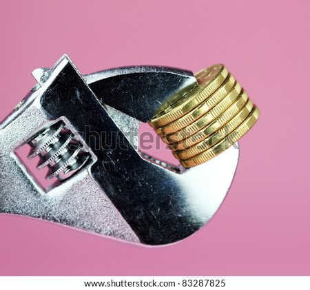 stack of Gold Dollar Coins being squeezed in a silver adjustable spanner, against a light pastel pink background and asking the questions how tight  is you household budget?