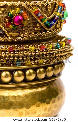 stack of golden bracelets closeup on white background