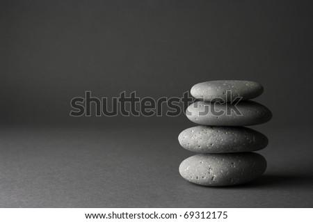Stack of grey massage stones on dark grey background.