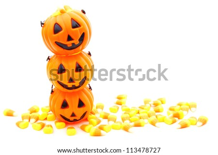 Stack of Halloween jack-o-lantern candy holders with candy corn over white