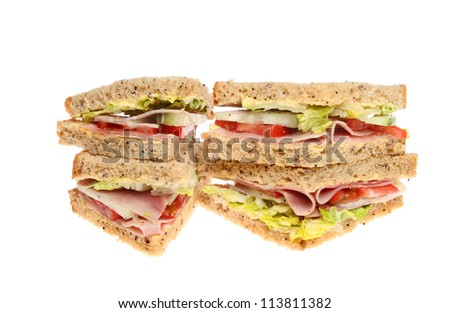 Stack of ham salad sandwiches with wholemeal bread isolated against white