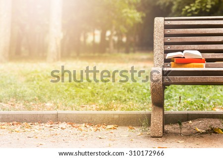 Stack of hardback book and Open book lying on a bench at sunset  park on blurred nature  backdrop. Copy space, back to school. Education background.