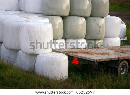Stack of hay bales wrapped in plastic and an empty trailer
