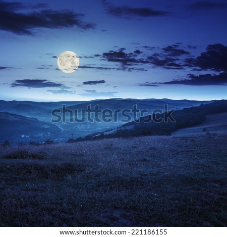 Stack of hay on a green meadow in the mountains in the morning under a blue summer sky at night in full moon light