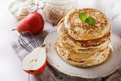 Stack of healthy low carbs oat pancakes over white wooden background