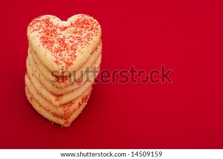 Stack of heart shaped cookies on a red background