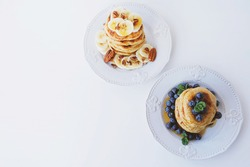 Stack of homemade small thick pancakes made with whole wheat flour served with fresh blueberry, mint, banana and pecan. Space for text. Traditional Eastern European dish. Sweet healthy food.