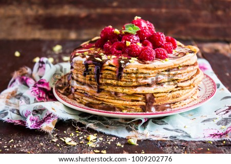 Shutterstock Stack of homemade thin pancakes or crepes or pancake cake with chocolate sauce, fresh raspberry, pistachios nuts decorated with fresh mint leaves on a plate, selective focus