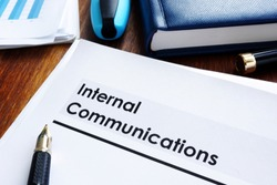 Stack of internal communications documents on a table.