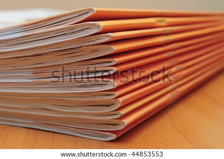 Stack of journals on office desktop. Shallow deep of field