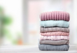 Stack of knitted textured clothing on table empty space.Colorful winter clothes,warm apparel.Heap of knitwear.Autumn garment.