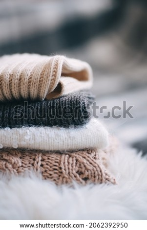 stack of knitted things on a light background. concept of warmth, comfort and coziness. winter-autumn mood.