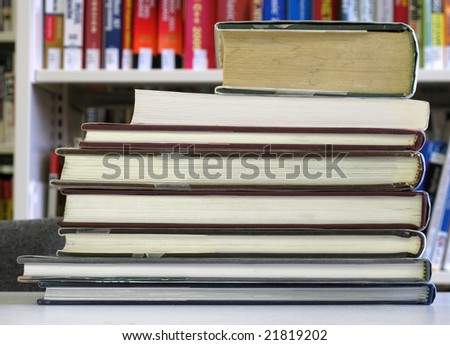 Stack of large books against a library shelf