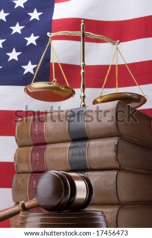 Stack of law books with gavel, scales of justice, and flag in background