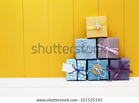Stack of little present boxes on yellow wooden wall #321535145