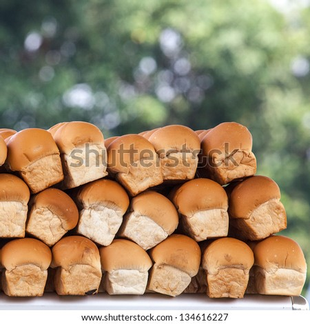 Stack of loaf against out focus green leaves background - stock photo