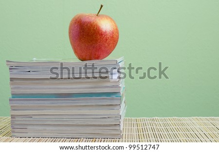 stack of magazines and red apple