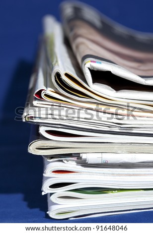 stack of magazines isolated on blue