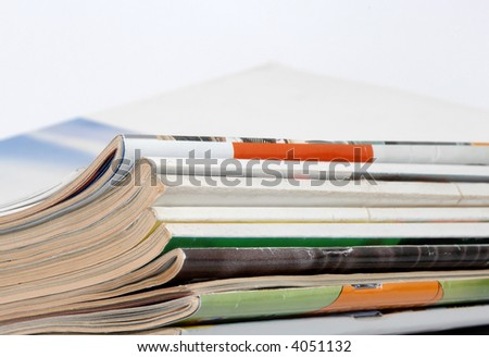 Stack of magazines on table in white background