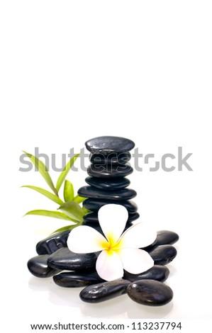 Stack of many black zen stone with white plumeria flower