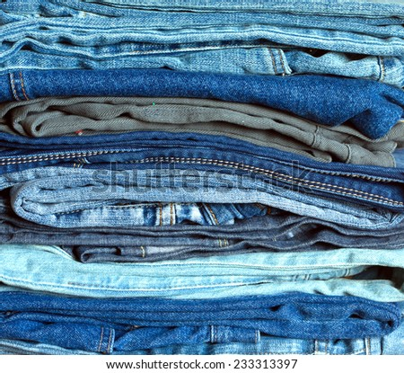 Stack of many colorful folded jeans with double yellow seams, front view close-up