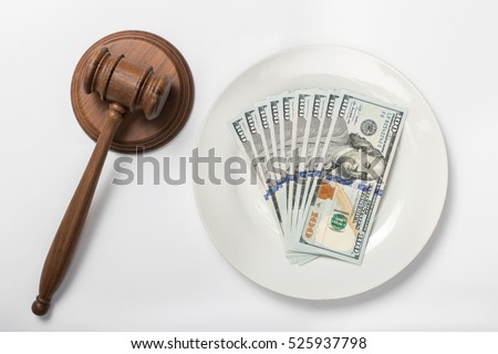 Stack of money on the plate on white background with a judge hammer, top view