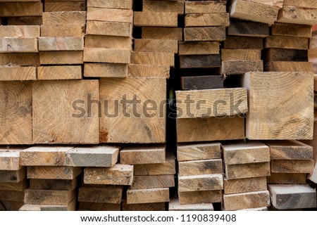 Stack of natural brown uneven rough wooden boards different size, cross-sectional view. Industrial timber for carpentry, building, repairing and furniture, lumber material for construction. #1190839408