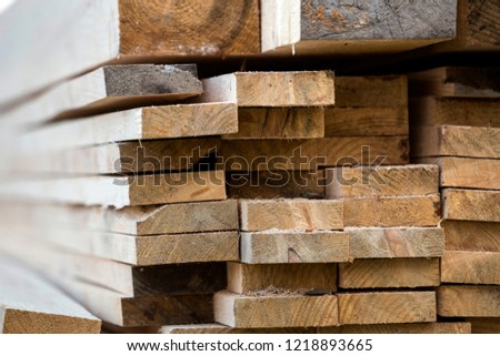 Stack of natural brown uneven rough wooden boards different size, cross-sectional view. Industrial timber for carpentry, building, repairing and furniture, lumber material for construction. #1218893665