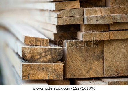 Stack of natural brown uneven rough wooden boards different size, cross-sectional view. Industrial timber for carpentry, building, repairing and furniture, lumber material for construction. #1227161896