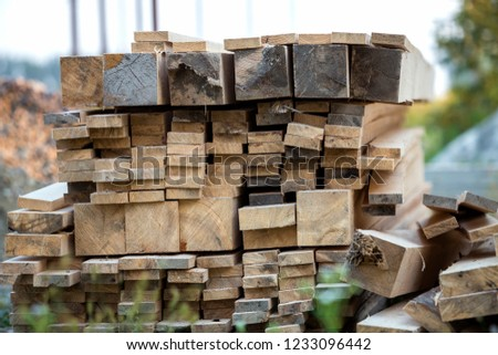 Stack of natural brown uneven rough wooden boards different size, cross-sectional view. Industrial timber for carpentry, building, repairing and furniture, lumber material for construction. #1233096442