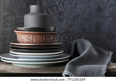 Stack of neutral colored dishware and linen napkin on distressed wooden shelf against rough plaster black wall. Kitchen utensils. #791200369