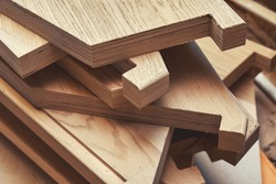 Stack of new details to assemble balanced steps for elegant stairs of plywood and solid beechwood in carpentry shop closeup