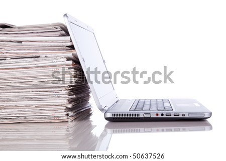 stack of newspaper next to a laptop (isolated on white)