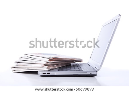 stack of newspaper over a laptop (selective focus)