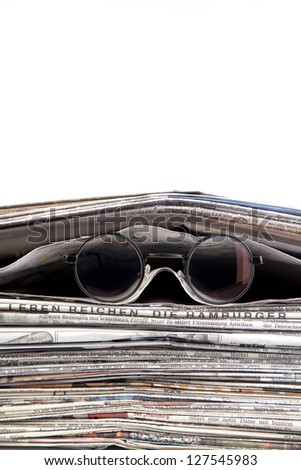 stack of newspaper with reading glasses