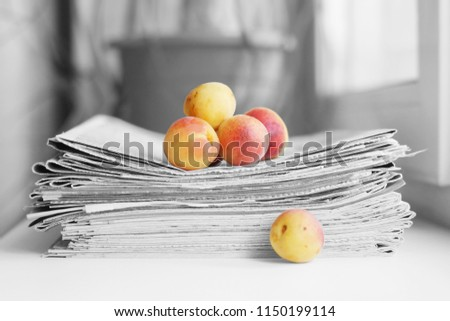 Stack of newspapers and apricots. Daily journals with headlines and articles and fresh fruits. Concept for juicy news       #1150199114