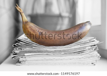 Stack of newspapers and banana. Daily journals with headlines and articles and rotten fruits. Concept for fake news                                   #1149576197