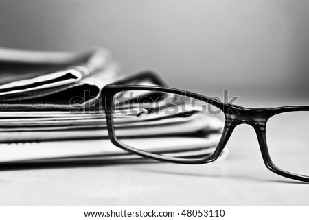 Stack of newspapers and glasses in black and white